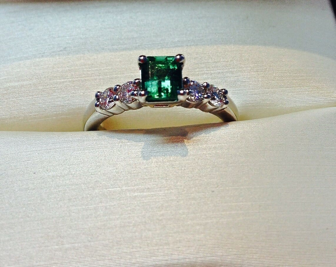 Emerald engagement ring featuring emerald cut center stone and four diamonds