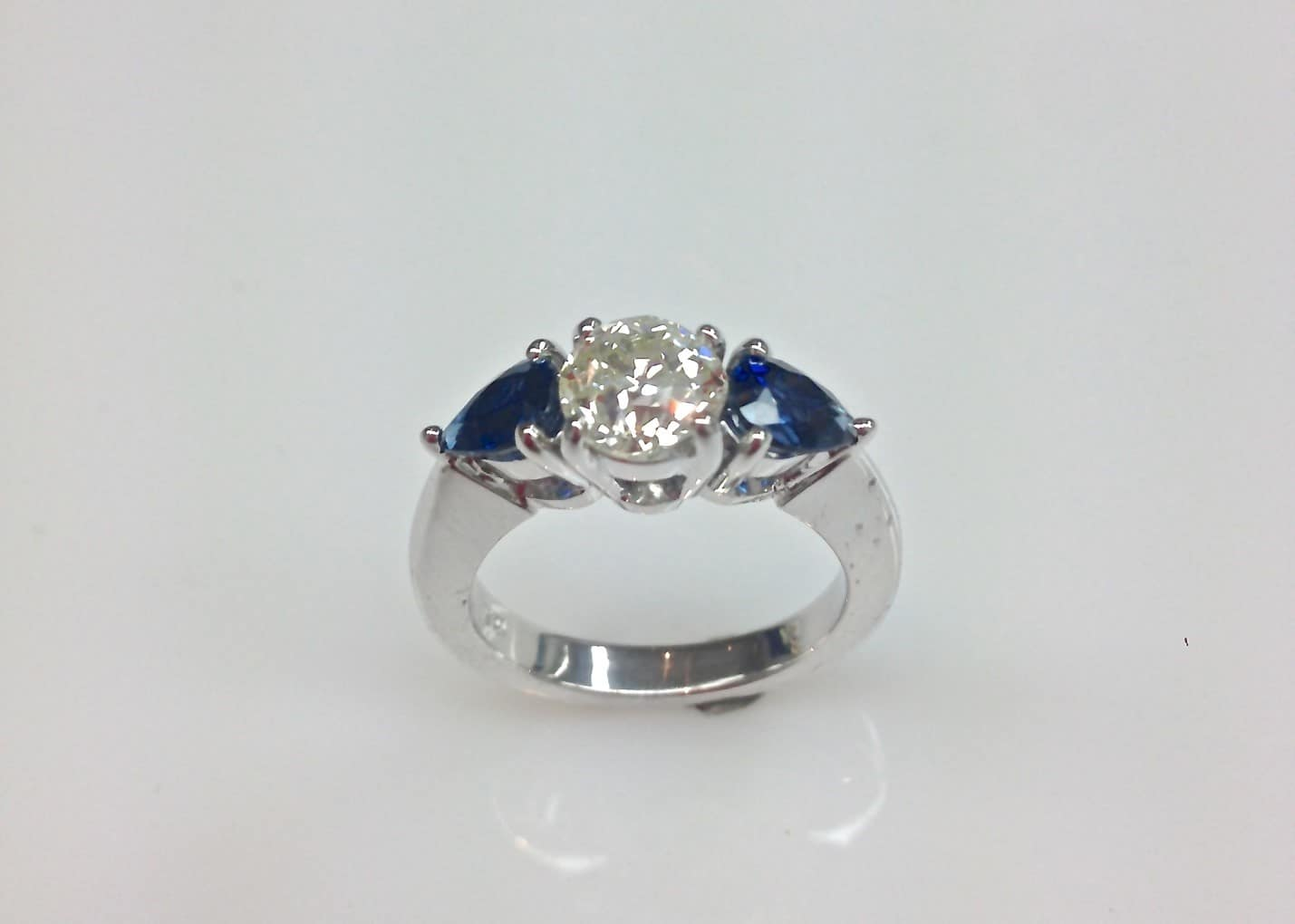 three stone sapphire engagement ring with trilliant cut sapphires