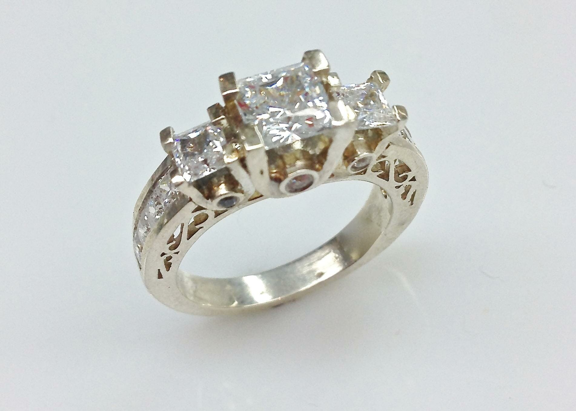 Princess cut three stone diamond engagement ring with carved detail