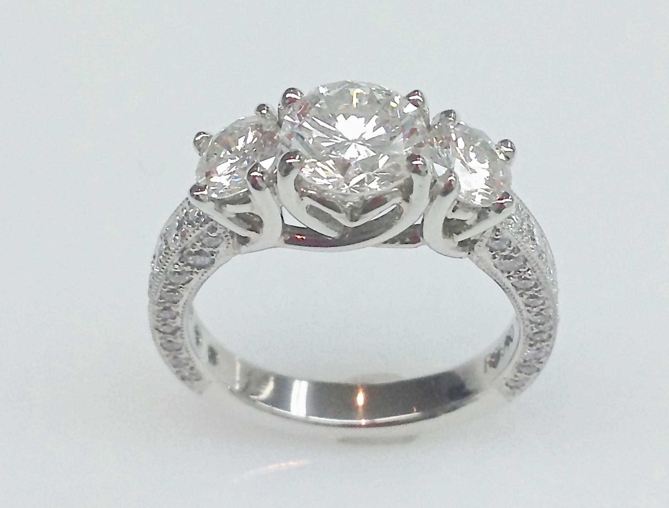 Platinum three stone diamond ring with pave diamond shank