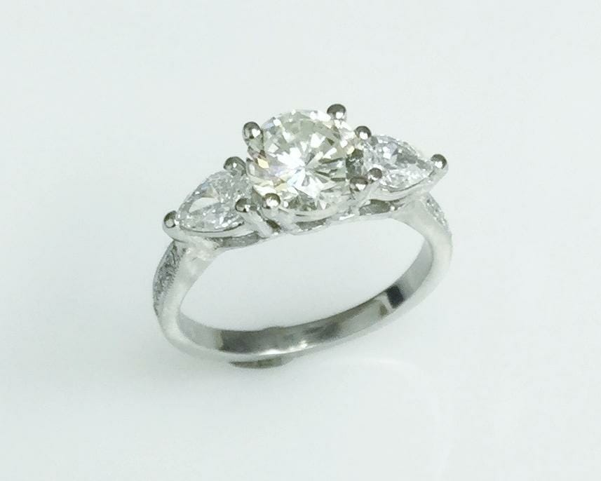 Round diamond ring with pear diamond side stones