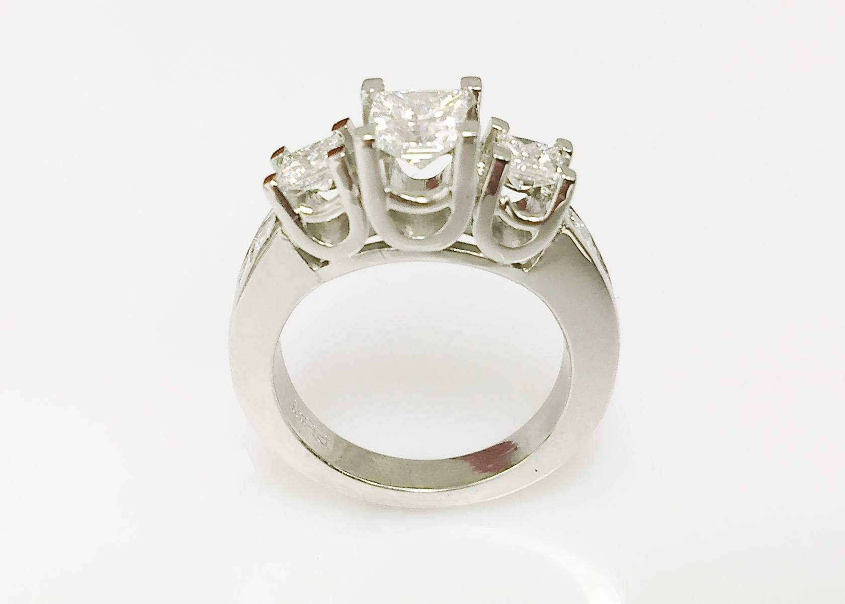 Mary platinum three stone ring with side diamonds front view