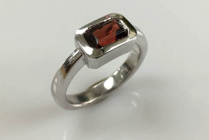 18k white gold bezel set garnet ring